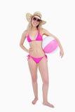 Adolescente sorridente in beachwear che tiene una sfera di spiaggia immagini stock