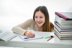 Adolescente sorridente che fa il suo compito fra la pila di libri Fotografie Stock