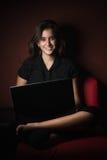 Adolescente sorridente che lavora al suo computer portatile Immagine Stock Libera da Diritti