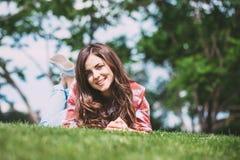 Adolescente sorridente che si trova sull'erba nel parco che esamina la macchina fotografica Fotografia Stock
