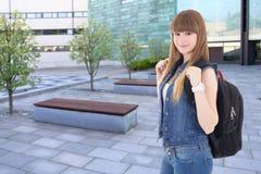 Adolescente sorridente che sta sulla via contro l'edificio scolastico Fotografie Stock Libere da Diritti