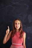 Adolescente sorridente davanti alla lavagna che indica spirito ascendente Fotografie Stock
