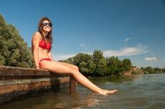 Adolescente sorridente grazioso che prende il sole sulla barca di fiume immagine stock