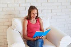Adolescente sorridente in poltrona bianca con un libro contro bianco Fotografie Stock