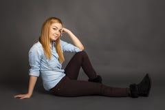 Adolescente sorridente sulla posa del pavimento Fotografia Stock