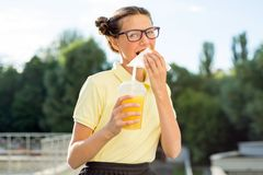 Adolescente sorridente sveglio in uniforme scolastico che tiene un hamburger e Fotografia Stock