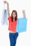 Adolescente souriant et soulevant ses sacs à provisions photo libre de droits