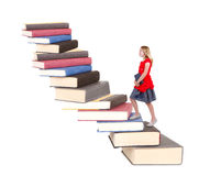 Adolescente subiendo una escalera de libros Foto de archivo