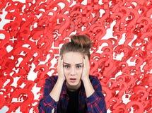 Adolescente subrayada contra signos de interrogación rojos Imagen de archivo libre de regalías