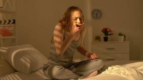 Adolescente subrayado que come la cama que se sienta del pan, bulimia joven de la edad, trastorno mental almacen de metraje de vídeo