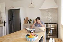 Adolescente subrayado que estudia con el ordenador en cocina Foto de archivo libre de regalías