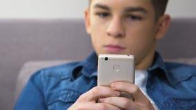 Adolescente subrayado que juega al videojuego rápido en el smartphone, gestión de la cólera de la escuela almacen de metraje de vídeo