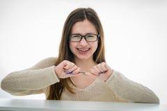 Adolescente subrayado que rompe su lápiz en dos Fotos de archivo libres de regalías