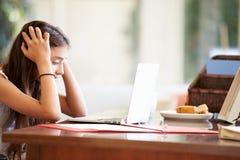 Adolescente subrayado que usa el ordenador portátil en el escritorio en casa Imagen de archivo libre de regalías