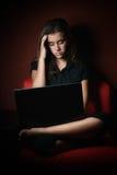 Adolescente subrayado y agotado que trabaja en un ordenador portátil Foto de archivo libre de regalías