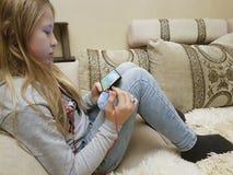 Adolescente sul sofà in smartphone delle cuffie Immagini Stock