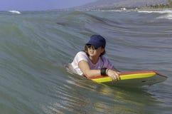 Adolescente sur le bodyboard rouge et jaune images stock