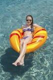 Adolescente sur le flotteur dans la piscine photos stock