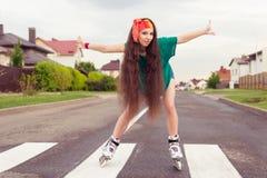 Adolescente sus brazos hacia fuera al rollerblading lateral Imagenes de archivo