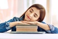 Adolescente sveglio che dorme su un mucchio dei libri Immagine Stock Libera da Diritti