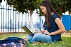 Adolescente sveglio che per mezzo di un computer portatile Fotografia Stock Libera da Diritti