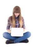 Adolescente sveglio che si siede con il computer portatile Fotografie Stock Libere da Diritti