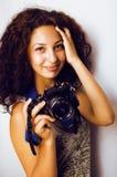 Adolescente sveglio piccolo con la macchina fotografica della tenuta dei capelli ricci, fotografo che prende un colpo, concetto d fotografia stock