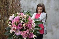 Adolescente tímido con el manojo de flores grande Fotos de archivo