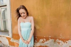 Adolescente tímido en el vestido del tubo que se opone a la pared Fotos de archivo