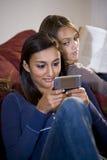 Adolescente texting mientras que relojes de la hermana Fotos de archivo libres de regalías