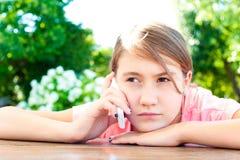 Adolescente tiene conversación al lado del teléfono móvil Fotografía de archivo