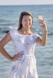 Adolescente tomando un Selfie en la playa, primer Imagen de archivo