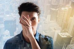 Adolescente tranquilo que guarda la mano izquierda delante de su cara Imagen de archivo libre de regalías