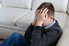 Adolescente trastornado 13 años, él se sienta cerca del sofá que cubre su cara con sus manos Imágenes de archivo libres de regalías