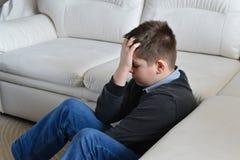 Adolescente trastornado 13 años que se sientan cerca del sofá y que llevan a cabo su cabeza en manos Foto de archivo