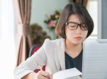 Adolescente travaillant sur l'ordinateur portable dans le siège social Images stock