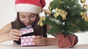 Adolescente travieso hermoso de la muchacha en un sombrero de Santa Claus que mira secretamente el regalo debajo del árbol del Añ Imagen de archivo libre de regalías