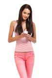 Adolescente trigueno con el teléfono móvil aislado en blanco Imágenes de archivo libres de regalías