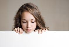 Adolescente trigueno joven magnífico con la muestra en blanco. Foto de archivo