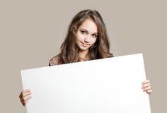 Adolescente trigueno joven magnífico con la muestra en blanco. Fotos de archivo libres de regalías