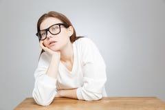 Adolescente triste aburrido en los vidrios que localizan en la tabla Fotos de archivo