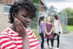 Adolescente triste che ritiene sinistro fuori dagli amici immagini stock
