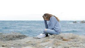 Adolescente triste che si siede sulla spiaggia in un giorno ventoso stock footage
