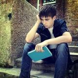 Adolescente triste con el libro Foto de archivo libre de regalías