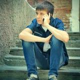Adolescente triste con el teléfono móvil Imágenes de archivo libres de regalías
