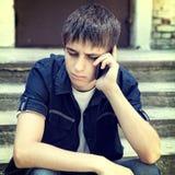 Adolescente triste con el teléfono móvil Fotografía de archivo libre de regalías