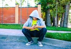 Adolescente triste con el teléfono móvil Foto de archivo libre de regalías