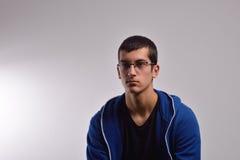 Adolescente triste con la camiseta azul que se opone a una pared sucia Foto de archivo libre de regalías