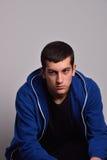 Adolescente triste con la camiseta azul que se opone a una pared sucia Imagen de archivo libre de regalías
