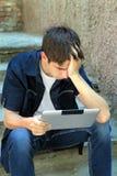 Adolescente triste con la tableta Fotografía de archivo libre de regalías